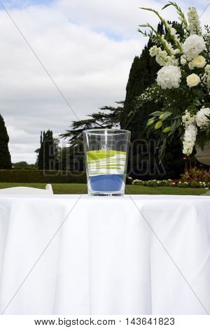 glass of mixed colour sands after a unity wedding celebration
