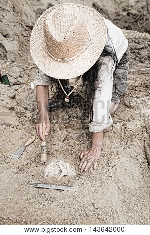 Archaeologist carefully revealing ancient human remains, toned image