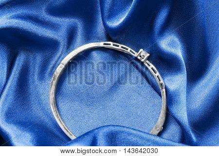 Silver bracelet on blue draped satin as a background