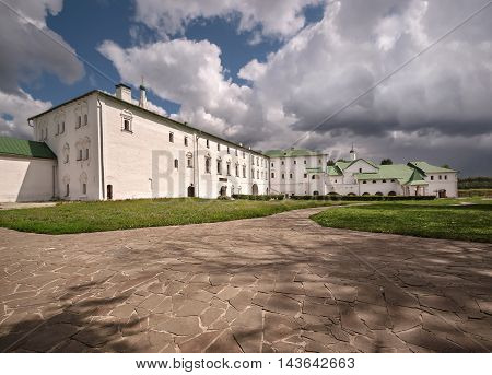The buildings of the old monastery in Suzdal, Russia. Green grass and stone slabs in the yard.