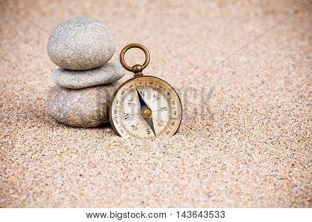 Vintage compass with three pebble stones on sand