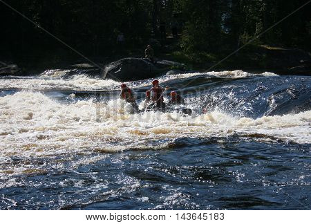KOLA PENINSULA RUSSIA - 17 AUGUST 2008: Team of men on an inflatable catamaran at rough river