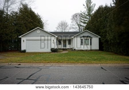 WEQUETONSING, MICHIGAN / UNITED STATES - DECEMBER 22, 2015: A small white home with an attached garage on Pennsylvania Avenue in Wequetonsing.