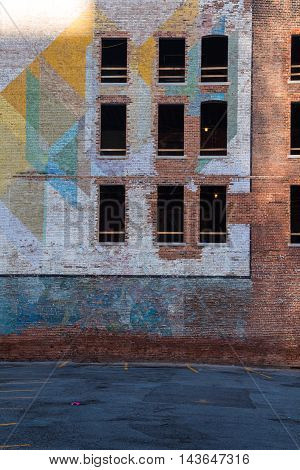 Old abandoned building in the downtown of Detroit. Facade made of bricks partly with a colorful painting. Broken windows.