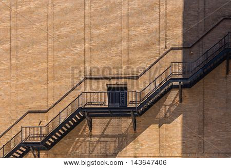 Side wall of a building made of bricks. Line of the outside staircase door in the middle. Line of light and shadow. Detroit USA