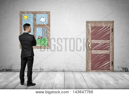 Back view of a businessman standing in front of the window looking at the door. Business staff. Office clothes.