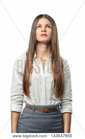 Young businesswoman looks upwards thoughtfully isolated on white background. Thinking process. Concepts and ideas. Business staff. Office clothes. Pondering and imagining.