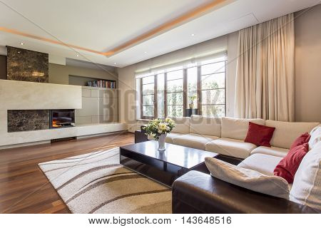 Luxurious living room in a villa with a leather corner sofa and a fireplace