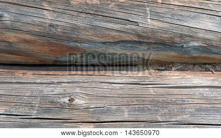 Timber industry concept - rough surface of gray weathered sawed wood logs of wooden house with cracks splits and scratchs closeup view