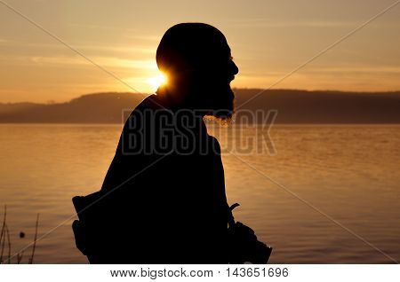 Old man as tourist with camera on Lake Constance at sunset silhouetted