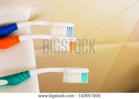Toothbrushes Laying Down Over Toilet Tiles Background With Copy Space