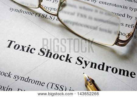 Paper with word Toxic Shock Syndrome  TSS and glasses. Medical concept.