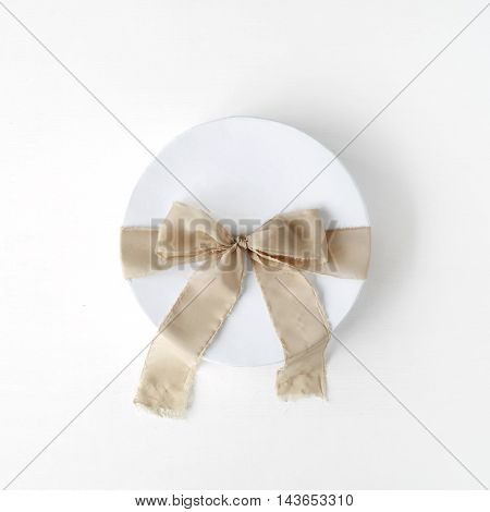 white gift cardboard box with brown bow on white background. flat lat top view