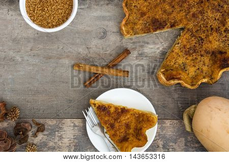 Homemade pumpkin pie on a rustic wooden background
