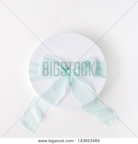 white gift cardboard box with blue bow on white background. flat lat top view