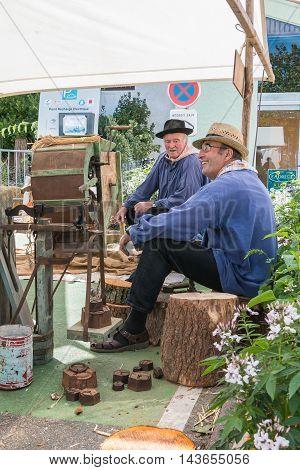 Men Sitting Next To An Ancient Machine To Thresh Grain
