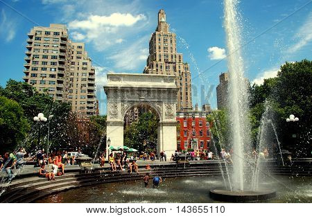 New York City - July 18 2009: The splashing fountain in Washington Square Park with the memorial George Washington Arch which marks the start of Fifth Avenue