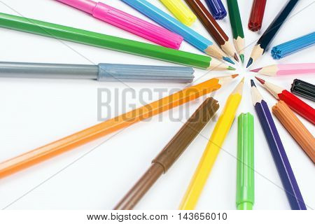 Colorful wooden pencils and felt pens on white background.