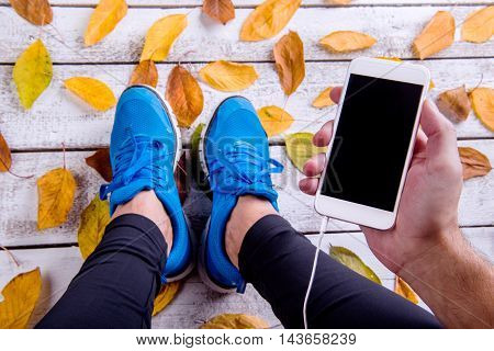 Runner In Sports Shoes Holding Smart Phone. Autumn Leaves.