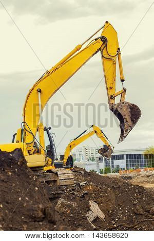 Two Excavators Are Digging Earth On The Construction Site.