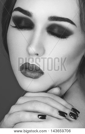 Beautiful young woman with smoky eyes and full red lips. Hands with dark nail polish. Studio beauty shot over blue background. Copy space. Monochrome.