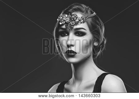 Beautiful young woman with smoky eyes and full red lips. Massive crystal hair accessory on head. Retro styling. Studio beauty shot. Copy space. Monochrome.