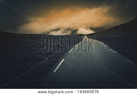 Uncertain Road Ahead. Dark and Cloudy Mountain Road Journey. Rocky Norway Landscape.