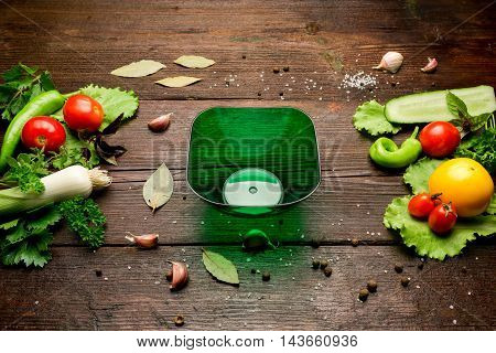 Fresh vegetables: tomatoes, cucumber, pepper, leek, salad, potherbs, spices and salad bowl on the dark wood table