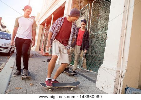 Positive teenage friends with skateboards riding down the street in summer day