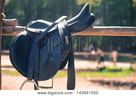 Horse saddle close up on stables fence out of focus background with people riding autumnal colors