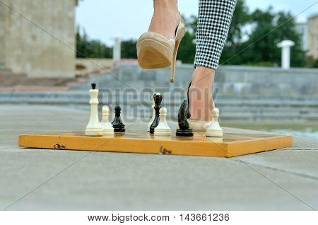 Closeup Of Legs Girls On A Chessboard.