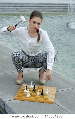 Woman Wants A Hammer To Break Pieces On A Chessboard.