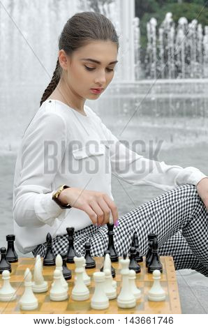 Girl Playing Chess Sitting Near The Fountain.
