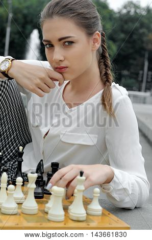 Girl Put Her Hand On A Chessboard.
