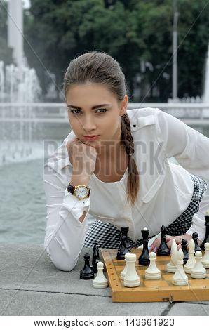 Woman Put A Fist Under Her Cheek While Playing Chess.