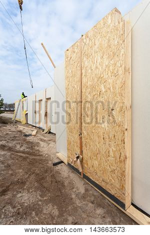 Roofer builder worker with crane installing structural Insulated Panels SIP. Building new frame energy-efficient house