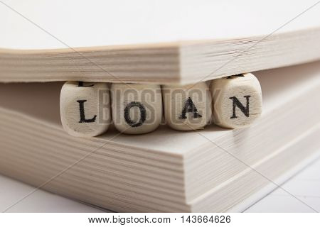 Wooden Blocks with text Loan and book pages.