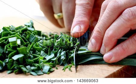 picture of a Cutting leek on wood chop board .