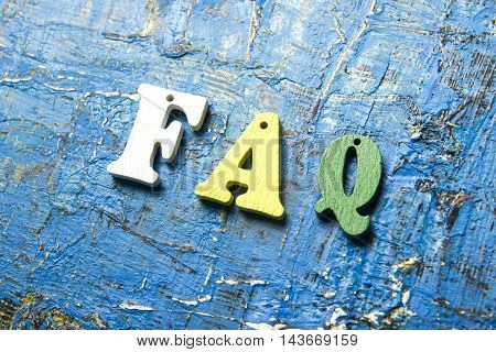 FAQ word written on wood colorful letters. Wooden abc at abstract blue grunge background.