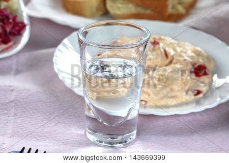 picture of a glass of rakia in front og kaymak