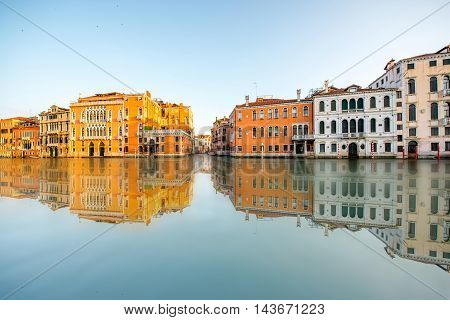 Beautiful waterfront with colorful buildings on Gran canal in Venice at the sunrise. Long exposure image technic with reflection on the water