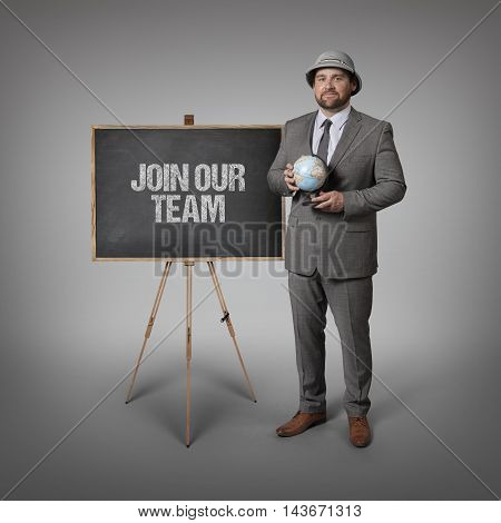 Join our team text on blackboard with businessman holding globe in hands