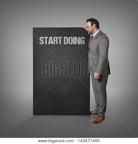 Start doing text on blackboard with businessman standing side