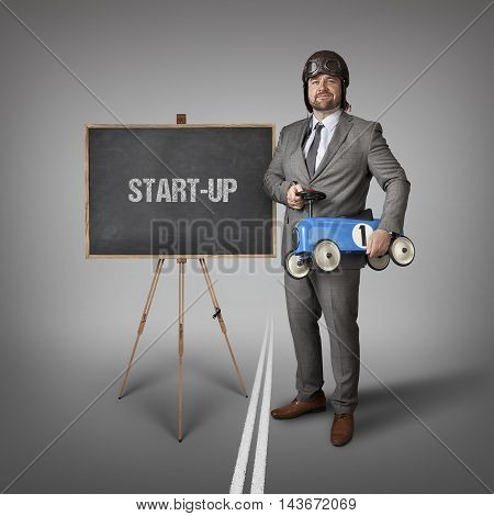 Start up text on blackboard with businessman and toy car