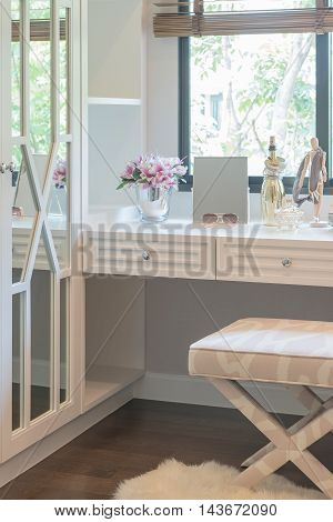White Dressing Table And Chair With Women's Accesories With Vase Of Flower
