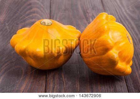 two yellow pattypan squash on a dark wooden table.