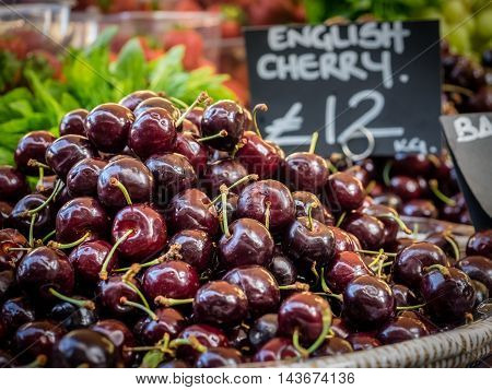 Pile of cherries on display on a stall at Borough Market in London, UK