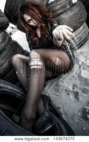 Disheveled Woman Between An Old Tires