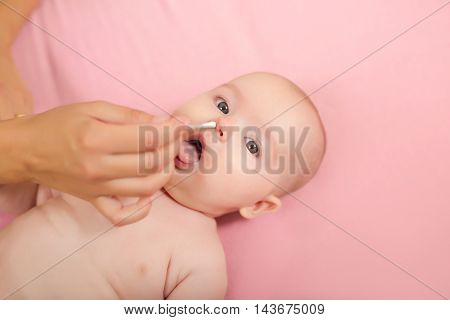 Woman hand cleans baby girl nose on the bad