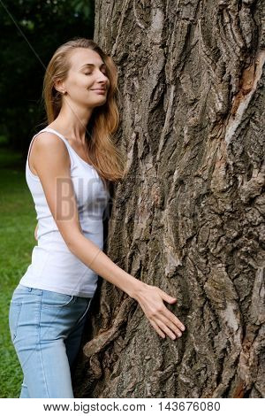 Young woman hugging big tree. Concept of love and nature protection